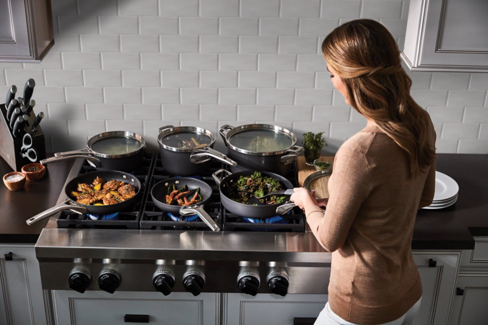 A woman in light-brown blouse using the Calphalon Premier™ Space Saving cookware to prepare meal