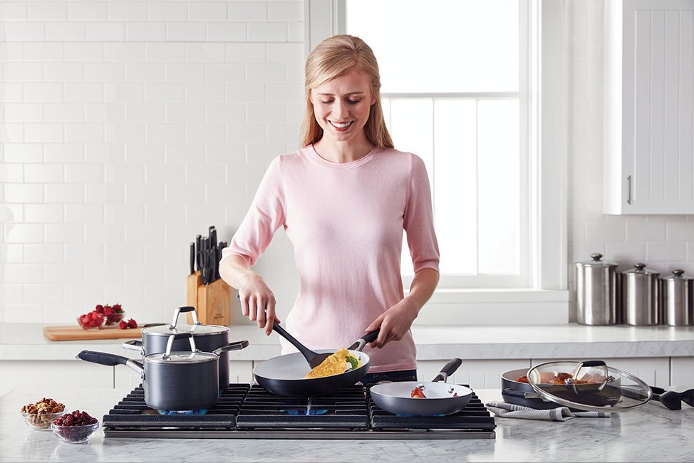 Woman in gray shirt cooking lunch with her Select By Calphalon Hard-Anodized Nonstick 14-Piece Cookware Set