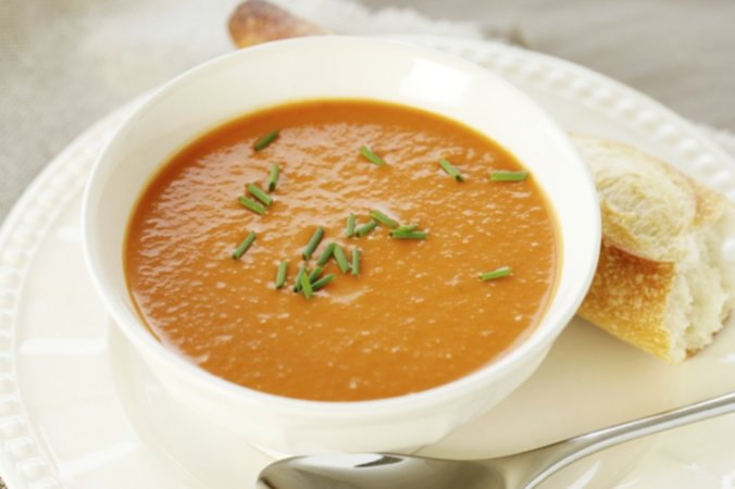 Curried butternut squash and apple soup with a fresh loaf of bread on white plate
