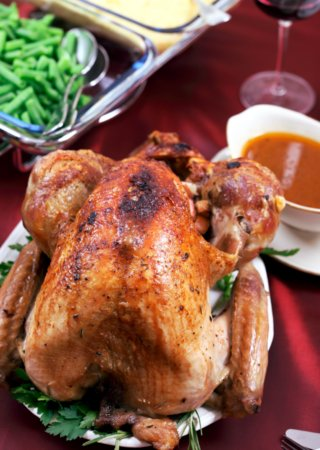 Roasted turkey and herbs on table with red tablecloth