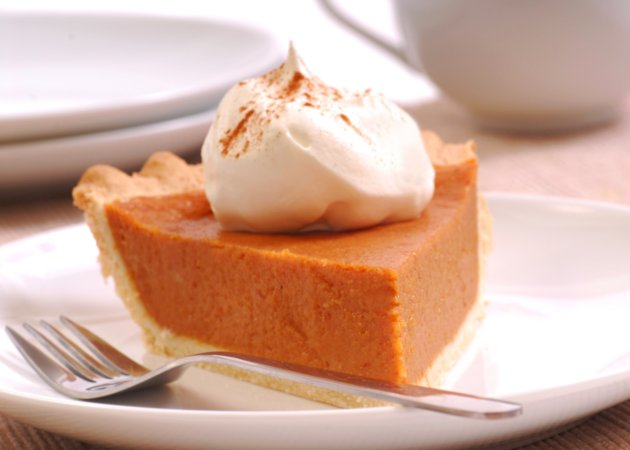 Made-from-scratch pumpkin pie with whipped cream on white plate